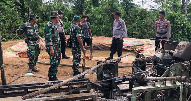 Petugas menutup sumur minyak illegal dan mengamankan barang bukti.