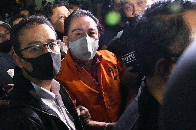 Anggota Bareskrim Mabes Polri mengawal tersangka tersangka korupsi, Djoko Tjandra selama kedatangannya di bandara Jakarta, Kamis (30/7) malam