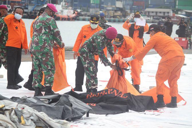 Petugas membawa kantong jenazah korban pesawat Sriwijaya Air SJ182.