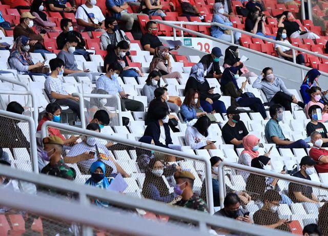 Masyarakat mengantre untuk melakukan vaksinasi Covid-19 massal di Stadion Utama Gelora Bung Karno, Senayan, Jakarta, Senin (5/07). Pemprov DKI Jakarta menggelar program Serbuan Vaksin Massal yang diperuntukan bagi warga minimal berusia 12 tahun guna mendukung program pemerintah pusat satu hari satu juta vaksinasi untuk menuju Indonesia sehat bebas COVID-19.