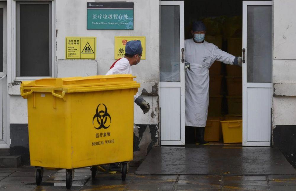 Seorang pekerja membawa gerobak penuh dengan limbah medis melewati kamar mayat, ke fasilitas penyimpanan di Rumah Sakit Youan di Beijing, kemarin.