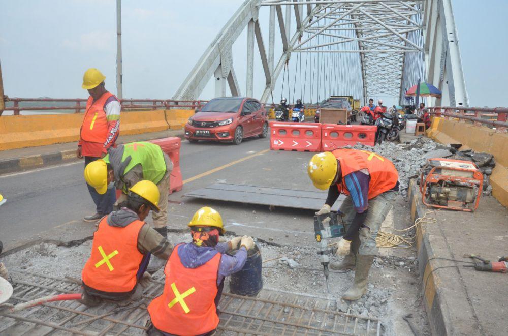 Pekerja saat melakukan perbaikan jalan di jembatan Batanghari II yang menghubungkan Kota Jambi dengan Muara Sabak di Tanjab Timur kemarin (10/9). Besok (12/9) jembatan akan ditutup total mulai pukul 20.00 - 06.00 WIB.